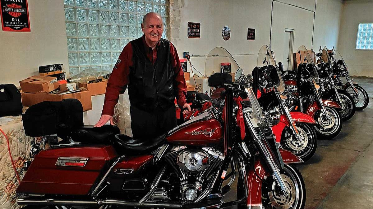 Law School alumnus Douglas Freedle stands with his collection of Harley Davidson motorcycles.