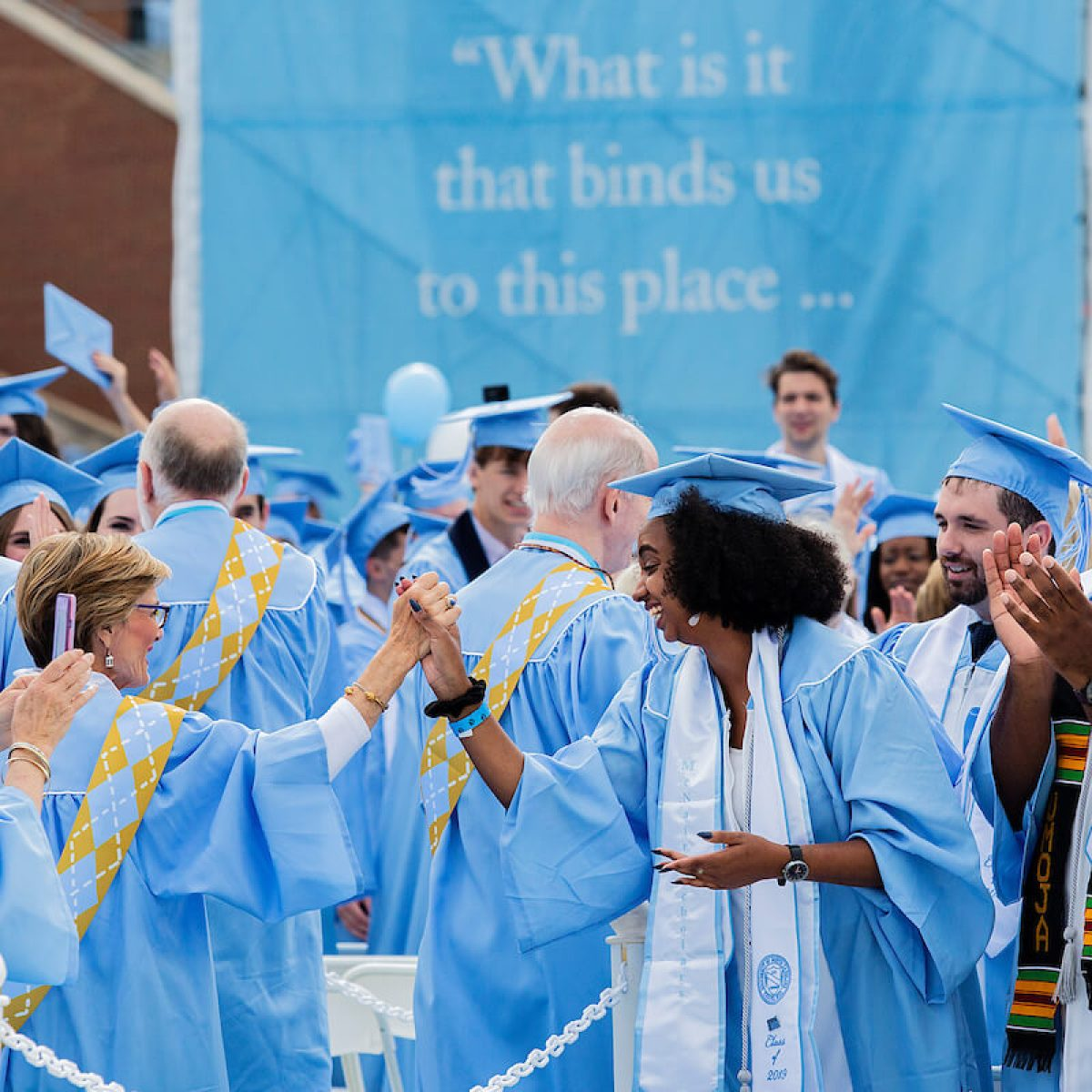 UNC-Chapel Hill graduates of various ages shake hands at the 2019 spring commencement ceremony