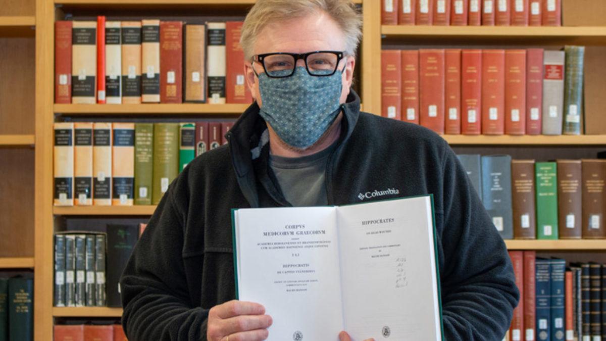 Professor Donald Haggis holds up a rare book.