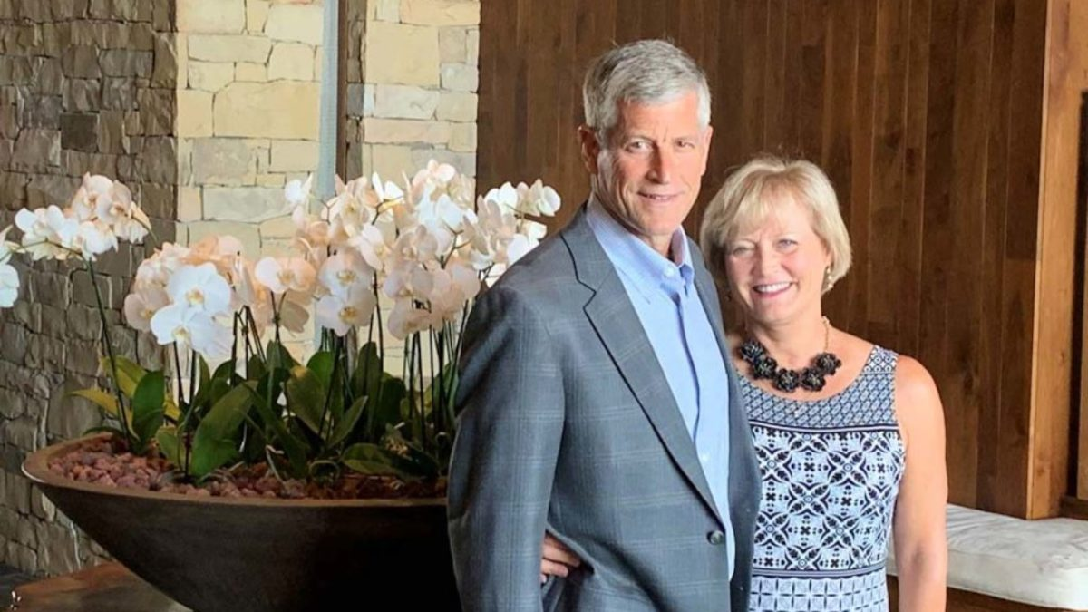 Rich and Tracy DeSelm pose in front of flowers.