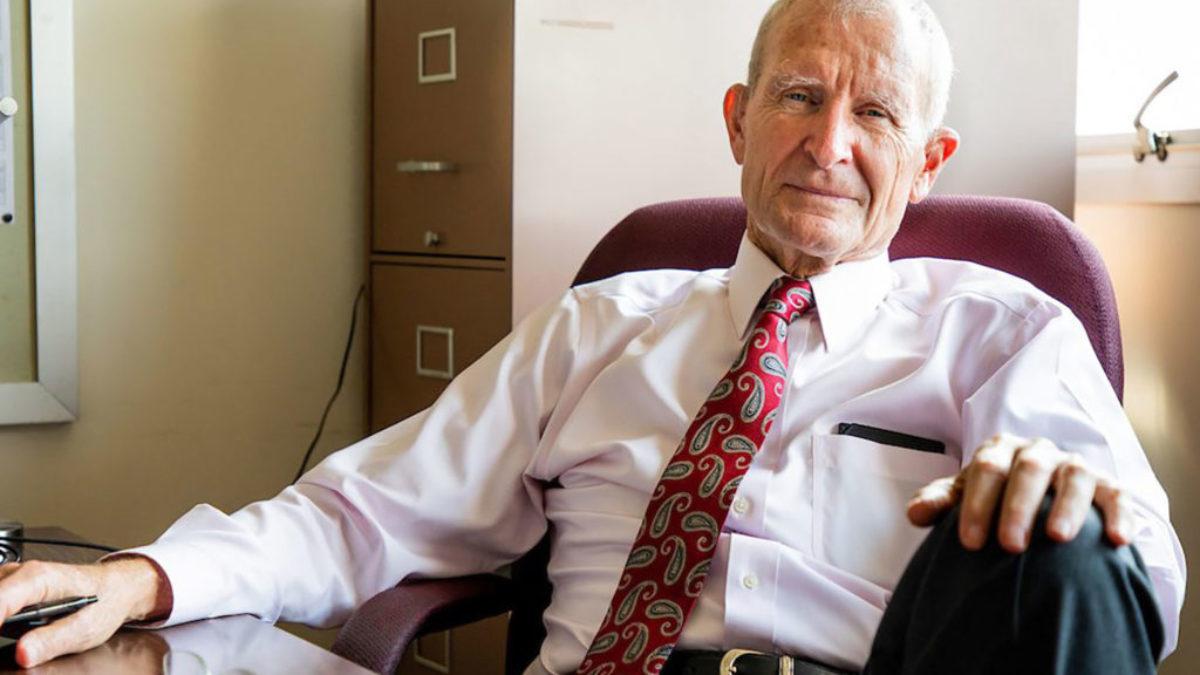 Admiral Dennis Blair sitting in chair in an office